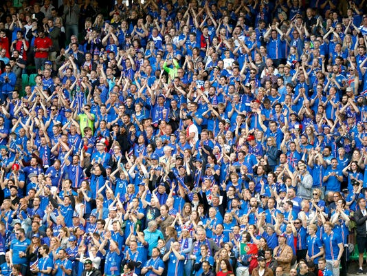 In this Tuesday, June 14, 2016 file photo Iceland's supporters cheer during the Euro 2016 Group F soccer match between Portugal and Iceland at the Geoffroy Guichard stadium in Saint-Etienne, France. Watching sport has always been popular among Icelanders, Iceland captain Aron Gunnarsson said Friday, June, 17,2016. Now their national football team is taking part in an international tournament for the first time, the fervor has risen to a whole new level. (AP Photo/Laurent Cipriani, File)