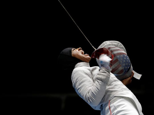 Ibtihaj Muhammad celebrates after winning a point to Russia in a women's team sabre fencing semifinal at the 2016 Summer Olympics in Rio de Janeiro, Brazil, Saturday, Aug. 13, 2016. (AP Photo/Andrew Medichini)