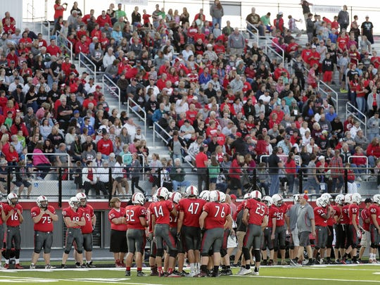 The Pulaski football team huddles up in front of the new grandstand against Sheboygan North at Saputo Stadium on Sept. 2.
