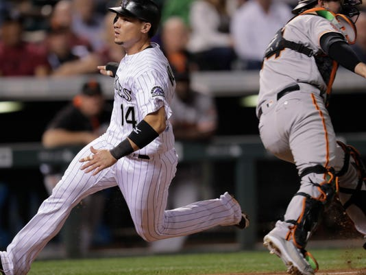 Colorado Rockies' Tony Wolters, left, scores on a sacrifice fly by Raimel Tapia as San Francisco Giants catcher Trevor Brown fields the throw during the fifth inning of a baseball game Tuesday, Sept. 6, 2016, in Denver. The Giants won 3-2. (AP Photo/David Zalubowski)