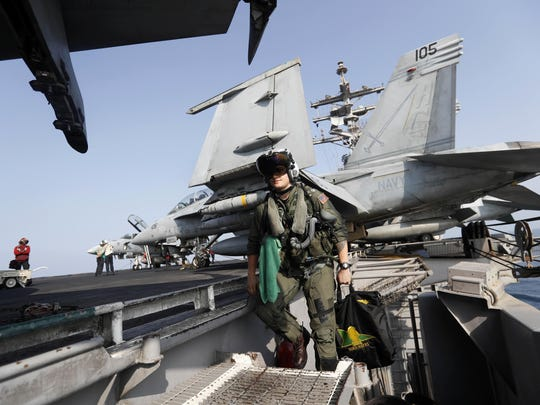 In this Nov. 22, 2016, file photo, Lt. Jennifer Sandifer, a 27-year old fighter pilot from Austin, Texas, walks towards F/A-18E Super Hornet jet before launching from the deck of the U.S.S. Dwight D. Eisenhower aircraft carrier towards targets in Iraq and Syria.