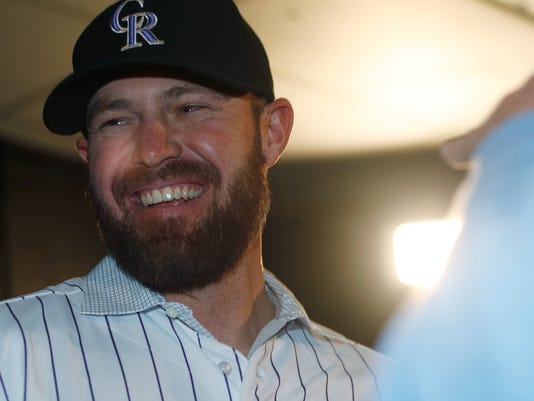 Newly signed Colorado Rockies relief pitcher Mike Dunn jokes with reporters after he was introduced at a news conference by the team Thursday, Dec. 15, 2016, in Denver. (AP Photo/David Zalubowski)