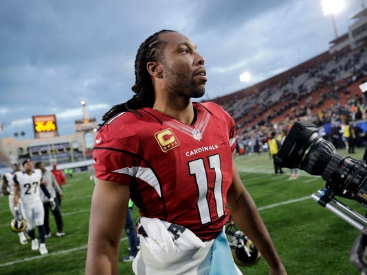 FILE - In this Jan. 1, 2017 file photo, Arizona Cardinals wide receiver Larry Fitzgerald walks off the field after a win over the Los Angeles Rams in an NFL football game in Los Angeles.  Fitzgerald has confirmed he will be back to play a 14th NFL season. In a text to azcardinals.com's Darren Urban, Fitzgerald confirmed a report that he had told ESPN's Jim Trotter on Wednesday, Feb. 1,  that he would play another season.  (AP Photo/Jae C. Hong)