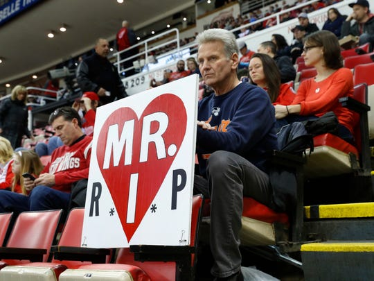 Hank Stawasz holds a sign in a tribute to Mike Ilitch at Joe Louis Arena before an NHL hockey game between the Detroit Red Wings and St. Louis Blues, Wednesday, Feb. 15, 2017, in Detroit. Billionaire businessman Ilitch, who founded the Little Caesars pizza empire before buying the Detroit Red Wings and Detroit Tigers died Friday. He was 87.