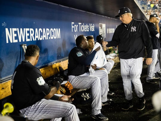New York Yankees pitching coach Larry Rothschild meets with pitcher Aroldis Chapman in the dugout after Chapman pitched in the fourth inning of a spring training baseball game against the Baltimore Orioles Thursday, March 2, 2017, in Tampa, Fla. (AP Photo/Matt Rourke)