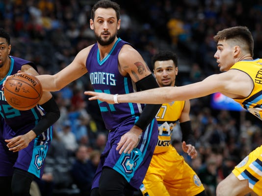 Charlotte Hornets guard Marco Belinelli, left, of Italy, drives to the net as Denver Nuggets forward Juancho Hernangomez, of Spain, defends in the first half of an NBA basketball game Saturday, March 4, 2017, in Denver. (AP Photo/David Zalubowski)
