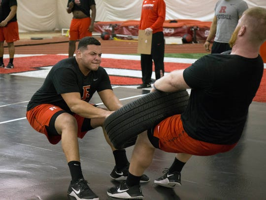 In this Feb. 15, 2017, photo provided by Rutgers Athletics, Rutgers NCAA college football players Jonah Jackson, left and Zach Venesky work out in Piscataway, N.J. Winter is rise and grind season in college football. Players cannot practice with coaches, but they can do conditioning training. For no more than eight hours a week, spread over no more than five days per week, they pump iron, sweat profusely and lay the foundation for what they hope will be a successful fall. (Carl Harris/Rutgers Athletics via AP)