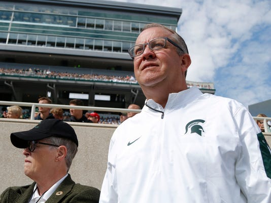 "FILE - In this Sept. 24, 2016, file photo, Michigan State University athletics director Mark Hollis, right, and president Lou Anna Simon watch the action during an NCAA college football game against Wisconsin, in East Lansing, Mich. Hollis, the chair of the NCAA selection committee, said Wednesday that the committee was restarting ""our season-long evaluation of teams"" instead of simply updating the preliminary rankings of the top 16 seeds released last month. (AP Photo/Al Goldis, File)"