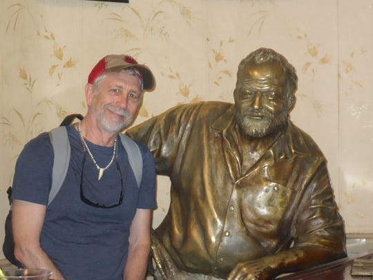 """The author poses with a statue of Ernest Hemingway in El Floridita, a bar known as the """"cradle of the daiquiri."""" Hemingway is said to have once consumed 13 grapefruit daiquiris in the bar."""