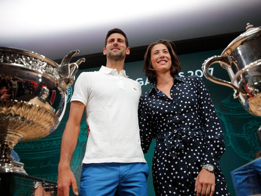 Defending champions Serbia's Novak Djokovic and Spain's Garbine Muguruza pose in front of the cups during the draw of the French Open tennis tournament at the Roland Garros stadium, Friday, May 26, 2017 in Paris. The French Open tennis tounament starts Sunday. (AP Photo/Christophe Ena)
