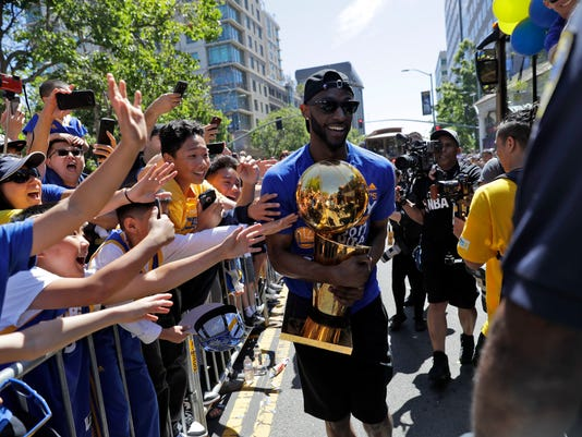 Golden State Warriors' Ian Clark holds the Larry O'Brien trophy during a parade and rally in honor of the Warriors, Thursday, June 15, 2017, in Oakland, Calif., to celebrate the team's NBA basketball championship. (AP Photo/Marcio Jose Sanchez)