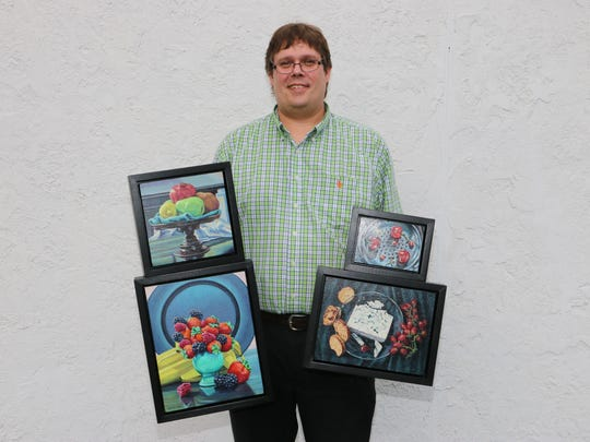 """Artist Kenneth Cobb holds four of his paintings that will be on display in the Gmeiner's Atrium Gallery. They are '""""Pedestal"""" (top left), """"Fruit Assortment"""" (bottom left), """"Cherries"""" (top right) and """"Midafternoon"""" (bottom right)."""