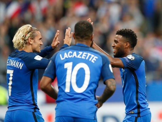 France's Thomas Lemar, right, celbrates with France's Antoine Griezmann and France's Alexandre Lacazette after scoring France' s third goal during the World Cup Group A qualifying soccer match between France and The Netherlands at the Stade de France stadium in Saint-Denis, outside Paris, Thursday, Aug.31, 2017. (AP Photo/Christophe Ena)