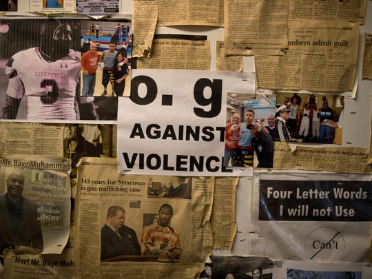 A flyer created by Old Gangsters Against Violence hangs on a wall with newspaper and magazine clippings at the Faith and Hope Community Center, on Aug. 21 in Syracuse, N.Y.