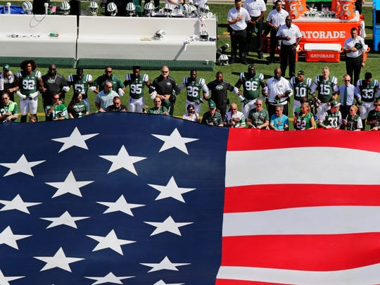 New York Jets head coach Todd Bowles joins his players as they lock arms during the playing of the national anthem before an NFL football game against the Miami Dolphins on Sunday, Sept. 24, 2017, in East Rutherford, N.J. (AP Photo/Frank Franklin II)