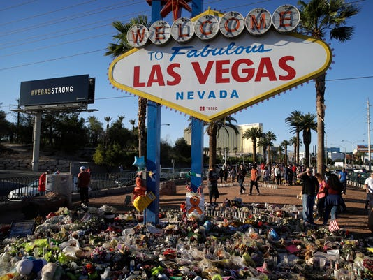Flowers, candles and other items surround the famous Las Vegas sign at a makeshift memorial for victims of a mass shooting Monday, Oct. 9, 2017, in Las Vegas. Stephen Paddock opened fire on an outdoor country music concert killing dozens and injuring hundreds. (AP Photo/John Locher)