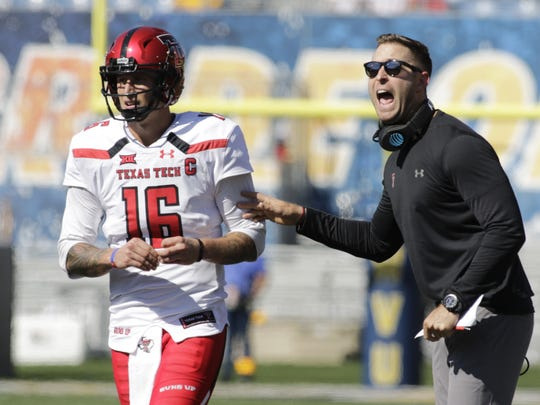 Texas Tech head coach Kliff Kingsbury gives instructions to quarterback Nic Shimonek (16) during the first half of an NCAA college football game against West Virginia, Saturday, Oct. 14, 2017, in Morgantown, W.Va. (AP Photo/Raymond Thompson)
