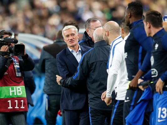 France's head coach Didier Deschamps, center, smiles after the World Cup Group A qualifying soccer match between France and Belarus at the Stade de France stadium in Saint-Denis, outside Paris, Tuesday, Oct.10, 2017. France won 2-1 to qualify for the 2018 soccer World Cup. (AP Photo/Christophe Ena)