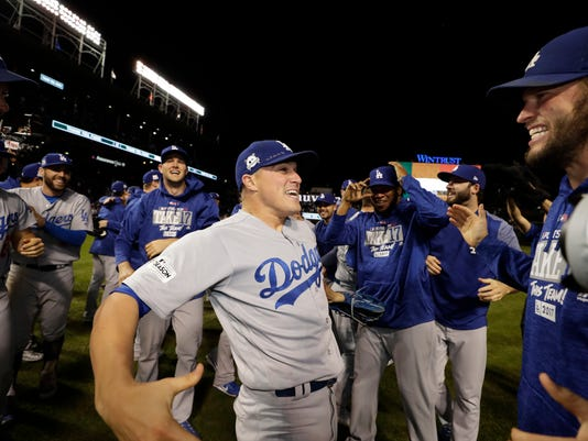 Los Angeles Dodgers' Enrique Hernandez celebrates with his teammates celebrate after Game 5 of baseball's National League Championship Series against the Chicago Cubs, Thursday, Oct. 19, 2017, in Chicago. The Dodgers won 11-1 to win the series and advance to the World Series. (AP Photo/Matt Slocum)