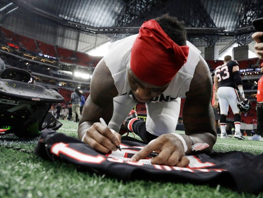Atlanta Falcons wide receiver Mohamed Sanu signs his jersey after an NFL football game between the Atlanta Falcons and the Tampa Bay Buccaneers, Sunday, Nov. 26, 2017, in Atlanta. The Atlanta Falcons won 34-20. (AP Photo/Chris O'Meara)