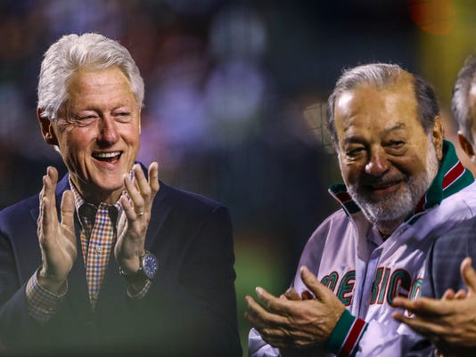 Former U.S. President Bill Clinton, left, and Mexican billionaire Carlos Slim applaud during the opening ceremony of the Caribbean Series baseball tournament in Guadalajara, Mexico, Friday, Feb. 2, 2018. (AP Photo/Luis Gutierrez)
