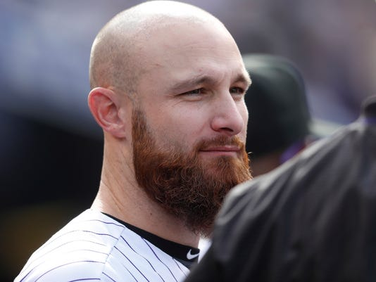 FILE - In this Oct. 1, 2017, file photo, Colorado Rockies catcher Jonathan Lucroy (21) is shown during the fourth inning of a baseball game against the Los Angeles Dodgers, in Denver. In a historically slow market, players and management are feuding publicly about riches and rules, and teams seemingly are seeking bargains like shoppers awaiting a closeout.  Job-seekers include pitchers Alex Cobb and Lance Lynn; reliever Greg Holland; infielder Eduardo Nunez; outfielders Carlos Gomez and Carlos Gonzalez; and catcher Jonathan Lucroy. (AP Photo/David Zalubowski, File)