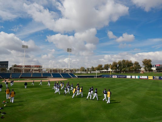 The Milwaukee Brewers take the field for warmup drills before batting practice at the team's spring training baseball facility Thursday, Feb. 15, 2018, in Maryvale, Ariz. (AP Photo/Carlos Osorio)