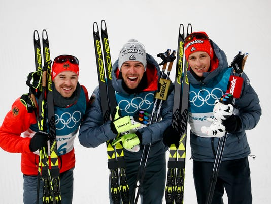 Gold medal winner Johannes Rydzek, of Germany, is flanked by silver medal winner Fabian Riessle, of Germany, left, and bronze medal winner Eric Frenzel, of Germany, during the venue ceremony after the men's 10km cross-country skiing competition in the large hill nordic combined event at the 2018 Winter Olympics in Pyeongchang, South Korea, Tuesday, Feb. 20, 2018. (AP Photo/Matthias Schrader)