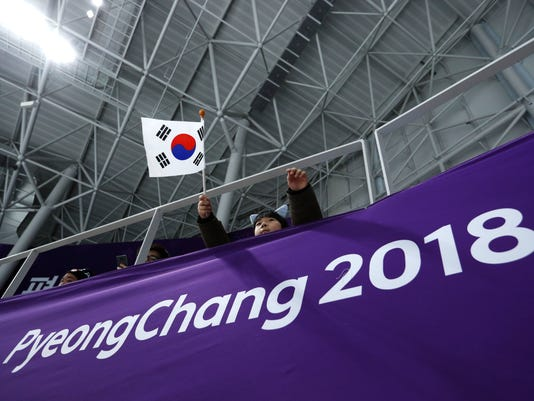 A spectator waves the South Korean flag during the finals of the men and women's team pursuit speedskating races at the Gangneung Oval at the 2018 Winter Olympics in Gangneung, South Korea, Wednesday, Feb. 21, 2018. (AP Photo/John Locher)