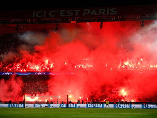 FILE - A Tuesday, March 6, 2018 file photo of PSG's fans holding flares during the round of 16, 2nd leg Champions League soccer match between Paris Saint-Germain and Real Madrid at the Parc des Princes Stadium in Paris. Paris Saint-Germain must close part of its stadium at its next Champions League home game as punishment for fans lighting flares and fireworks.UEFA says the north end of Parc des Princes will close due to incidents at PSG's 2-1 loss against Real Madrid this month, eliminating the French club from the Round of 16. (AP Photo/Francois Mori, File)