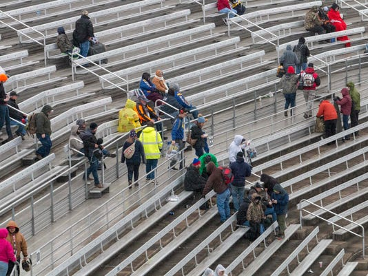Fans leave after rain cancelled the NASCAR Trucks Series auto race at Martinsville Speedway in Martinsville, Va., Saturday, March 24, 2018. (AP Photo/Matt Bell)