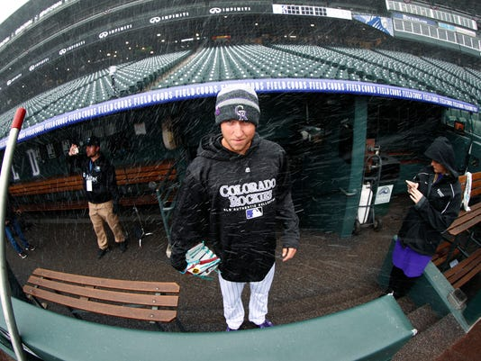 Colorado Rockies starting pitcher Kyle Freeland, a native of Denver, is caught in a blast of snow as he looks out of the dugout before the Rockies host the Atlanta Braves in a baseball game Friday, April 6, 2018, in Denver. (AP Photo/David Zalubowski)