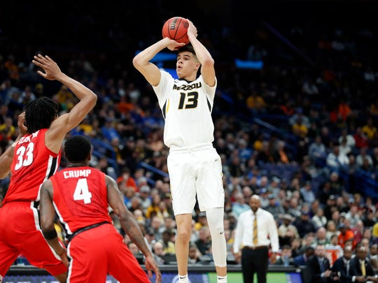 FILE - In this March 8, 2018, file photo, Missouri's Michael Porter Jr. shoots over Georgia's Nicolas Claxton (33) and Tyree Crump (4) during the first half in an NCAA college basketball game at the Southeastern Conference tournament in St. Louis. Porter was considered by many as last year's top recruit with his scoring, playmaking ability and athleticism. Porter and Marvin Bagley III will likely be the first forwards to hear their names called during Thursday's NBA Draft. (AP Photo/Jeff Roberson, File)