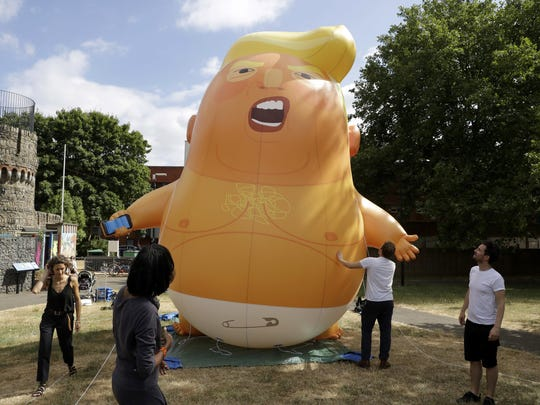 In this photo taken on Tuesday, July 10, 2018, a six-meter high cartoon baby blimp of U.S. President Donald Trump stands inflated during a practice session in Bingfield Park, north London. Trump will get the red carpet treatment on his brief visit to England that begins Thursday: Military bands at a gala dinner, lunch with the prime minister at her country place, then tea with the queen at Windsor Castle before flying off to one of his golf clubs in Scotland. But trip planners may go out of their way to shield Trump from viewing another aspect of the greeting: an oversize balloon depicting the president as an angry baby in a diaper that will be flown from Parliament Square during what are expected to be massive gatherings of protesters opposed to Trump's presence. (AP Photo/Matt Dunham)