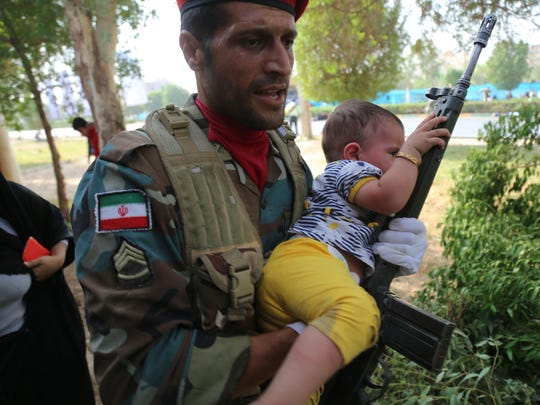 An image made available by Iran's Mehr News agency on September 22, 2018, shows an Iranian soldier carrying a child at the site of an attack on a military parade in the southwestern Iranian city of Ahvaz.