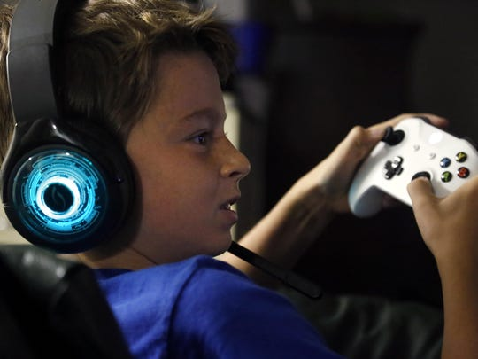 In this Saturday, Oct. 6, 2018, photo, Henry Hailey, 10, plays the online game Fortnite in the early morning hours in the basement of his Chicago home. His parents are on a quest to limit screen time for him and his brother. The boys say they understand sometimes, but also complain that they get less screen time than their friends. (AP Photo/Martha Irvine)
