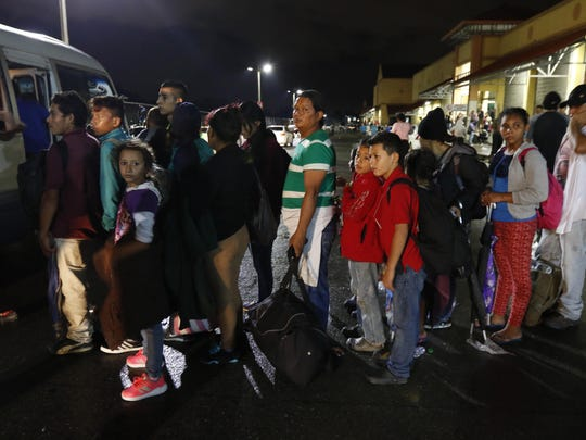 Migrants hoping to reach the U.S. wait in line to board a bus toward Honduras' border with Guatemala, as hundreds of migrants set off by bus or on foot from a main bus station in San Pedro Sula, Honduras, late Monday, Jan. 14, 2019.