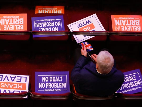 Attendees take their seats covered in placards at a political rally entitled 'Lets Go WTO' hosted by pro-Brexit lobby group Leave Means Leave in London on Jan. 17, 2019.