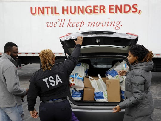 TSA employee Princess Young, center, loads food into a car after visiting a food pantry for furloughed government workers affected by the federal shutdown, Wednesday, Jan. 23, 2019, in Baltimore.