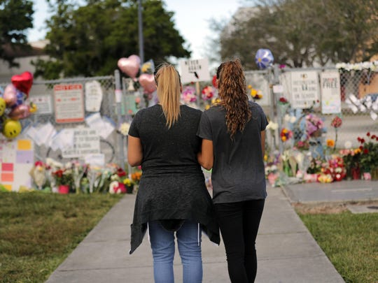 FILE- In this Feb. 19, 2018, file photo Sara Smith, left, and her daughter Karina Smith visit a makeshift memorial outside the Marjory Stoneman Douglas High School, where 17 students and faculty were killed in a mass shooting in Parkland, Fla. There have been more than 415 incidents of gunfire on U.S. school grounds since 2013, according to Every Town for Gun Safety, a nonprofit aimed at reducing domestic gun violence. Last year's carnage at Marjory Stoneman Douglas High School surpassed the 1999 Columbine High School massacre as the deadliest high school shooting in U.S. history. (AP Photo/Gerald Herbert, File )
