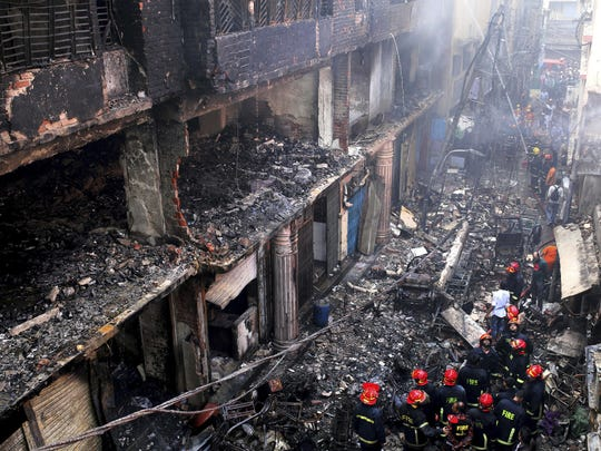 Locals and firefighters gather around buildings that caught fire late Wednesday in Dhaka, Bangladesh, Thursday, Feb. 21, 2019. A devastating fire raced through at least five buildings in an old part of Bangladesh's capital and killed scores of people.