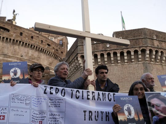 Survivors of sex abuse hold a cross as they gather during a twilight vigil prayer near Castle Sant' Angelo, in Rome, Thursday, Feb. 21, 2019. Pope Francis opened a landmark sex abuse prevention summit Thursday by warning senior Catholic figures that the faithful are demanding concrete action against predator priests and not just words of condemnation. (AP Photo/Gregorio Borgia)