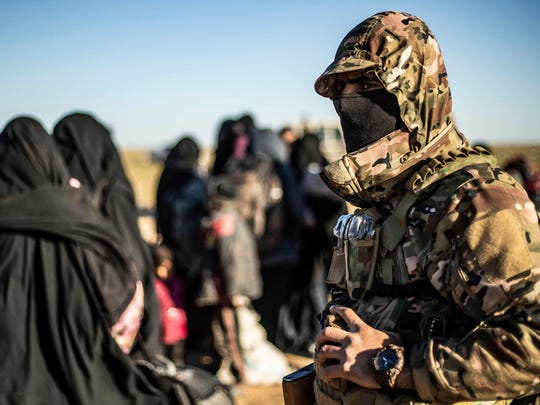 A Kurdish-led forces member stands by as women and children leave the Islamic State's last holdout of Baghouz in Syria.
