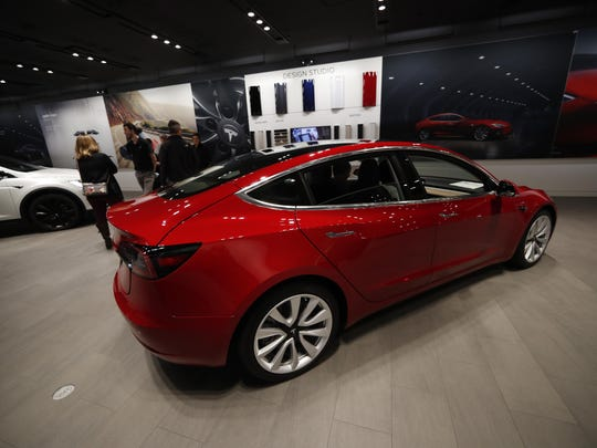 In this Saturday, Feb. 9, 2019, file photograph, buyers look over a Model 3 in a Tesla store in Cherry Creek Mall in Denver. The NHTSA is dispatching investigators to a fatal crash involving a Tesla electric car that drove beneath a semitrailer that was crossing a Florida roadway.