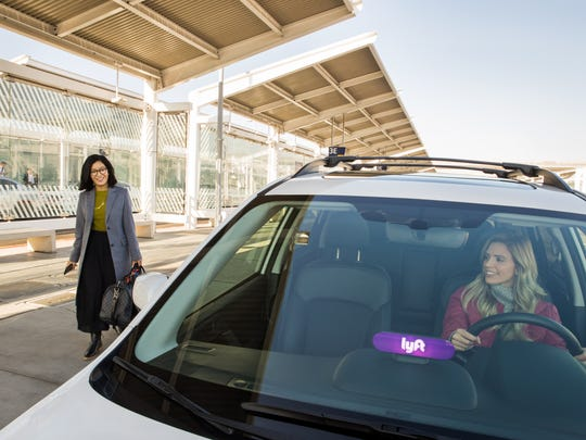 Woman walking near a car with a Lyft sign on the dashboard
