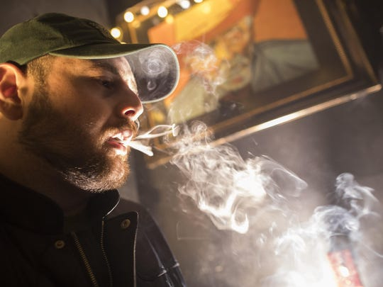 A man smokes marijuana at a Spleef NYC canna-cocktail party in New York. As more states make it legal to smoke marijuana, some government officials, researchers and others worry what that might mean for one of the country's biggest public health successes: curbing cigarette smoking.