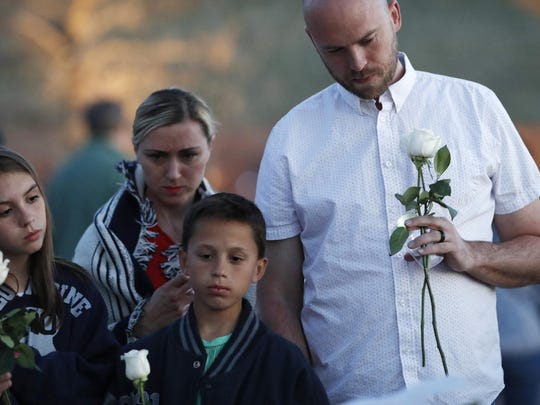 Will Beck, right, who escaped during the shooting attack nearly 20 years ago, joins his family during a vigil at the memorial for the victims of the massacre Friday, April 19, 2019, in Littleton, Colo.