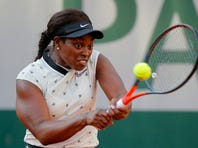 A person in the stands holds a large tennis ball as Sloane Stephens of the U.S. eyes the ball as she plays a shot against Slovenia's Polona Hercog during their third round match of the French Open tennis tournament at the Roland Garros stadium in Paris, Friday, May 31, 2019. (AP Photo/Pavel Golovkin)