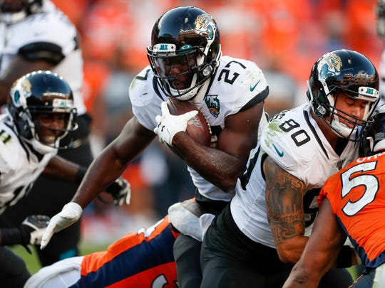 Jacksonville Jaguars running back Leonard Fournette, center, runs with the ball during the second half of an NFL football game against the Denver Broncos, Sunday, Sept. 29, 2019, in Denver. (AP Photo/David Zalubowski)
