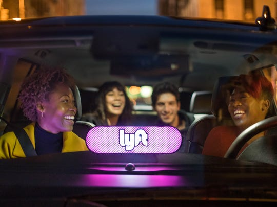 A driver and three other people in a car with a Lyft sign on the dashboard.